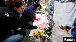 20일 미국 보스턴 테러 현장을 찾은 주민들이 희생자를 추모하는 메시지를 적고 있다.