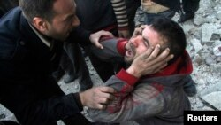 A man reacts after what activists said was an air raid by forces loyal to Syrian President Bashar Al-Assad, in Aleppo's al-Marja district December 23, 2013.
