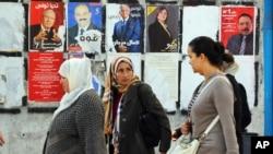 Perempuan-perempuan Tunisia melewati poster-poster kampanye pemilihan presiden di Tunis (21/11). (AP/Hassene Dridi)