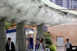 Beberapa orang mendinginkan diri di bawah pendingin udara di Tokyo, Jepang, Senin, 13 Juli 2018. (Foto: dok).
