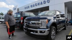 FILE - A potential customer looks at a Ford F-250 Lariat FX4 at a Ford dealership, in Hialeah, Florida, Jan. 17, 2017.