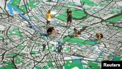 Artists work on a giant city map of Berlin that is drawn on a concrete square in central Berlin, Germany, August 2, 2012.