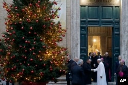 Pope Francis greets a priest as he leaves Sant' Andrea Delle Fratte church following a private visit, in Rome, Dec. 7, 2017.
