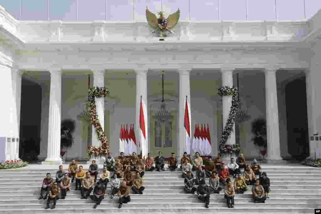 Presiden Joko Widodo (baris atas ke-5 dari kiri) dan Wakil Presiden Ma'ruf Amin (ke-6 dari kiri) bersama menteri-menteri kabinet baru duduk di tangga saat mengumumkan nama menteri-menteri baru, Rabu, 23 Oktober 2019. (Foto: AP)