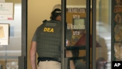 FILE - A Drug Enforcement Administration officer walks into a medical clinic in Little Rock, Arkansas, May 20, 2015.