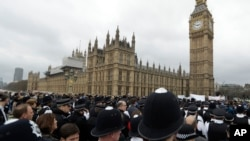 FILE - Police officers take part in a commemorative event to mark the attack outside Parliament that has now killed five people on Westminster Bridge in London, March 29, 2017.