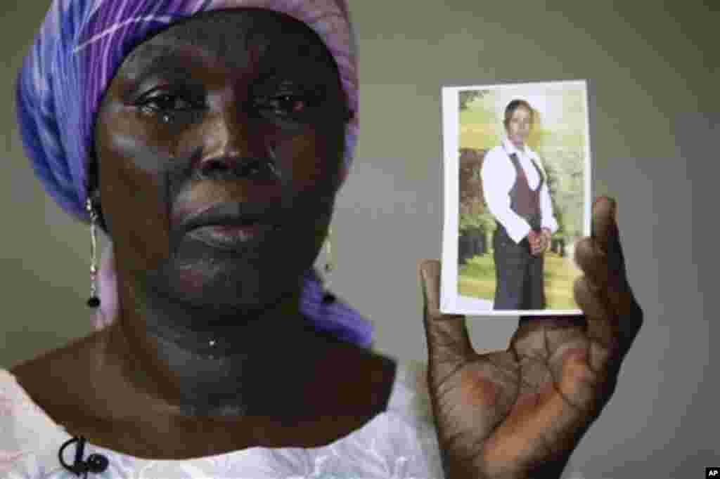 FILE - In this Monday, May 19, 2014 file photo, Martha Mark, the mother of kidnapped school girl Monica Mark cries as she displays her photo, in the family house, in Chibok, Nigeria. At least 11 parents of the more than 200 kidnapped Nigerian schoolgirls