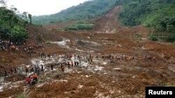 Tentara dan tim SAR berjalan melewati lumpur dalam upaya pencarian korban tanah longsor di desa Sampang, Banjarnegara (13/12).