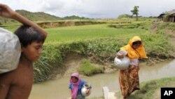 រ៉ូហីងគ្ហីយ៉ាស (Rohingyas) ដងទឺកពីថ្លុកមួយនៅក្បែរជំរុំជនភៀសខ្លួនមួយនៅក្នុងភូមិ Cox's Bazar, ប្រទេសបង់គ្ហ្លាដេសនៅថ្ងៃទី១៩ខែសីហាឆ្នាំ២០១១។