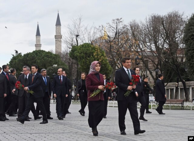 Turkey's Prime Minister Ahmet Davutoglu, right, accompanied by his wife Sare, visit the site of Tuesday's explosion, in the historic Sultanahmet district of Istanbul, Wednesday, Jan. 13, 2016.