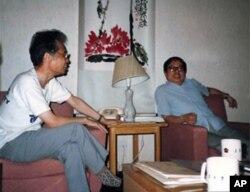 """1988年7月10日,宇宙学及粒子物理会议期间,何祚庥(左),方励之在徐一鸿教授房间(南京大学中美文化中心)讨论时局。方正在向何祚庥""""进行反革命宣传及鼓动反革命活动"""",是为首条罪行。"""