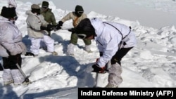 An Indian army soldier cuts through ice and snow in the search for survivors after a deadly avalanche on the Siachen Glacier, Feb. 8, 2016. An Indian soldier was rescued Monday, six days after being buried in the avalanche.