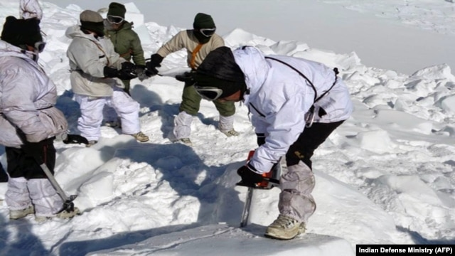 An Indian army soldier cuts through ice and snow in the search for survivors after a deadly avalanche on the Siachen glacier, Feb. 8, 2016. An Indian soldier was rescued Tuesday, six days after being buried in the avalanche.