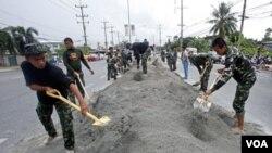 Tentara Thailand dikerahkan untuk membuat tanggul-tanggul pasir guna mencegah masuknya banjir di kawasan Pathum Thani, Bangkok.