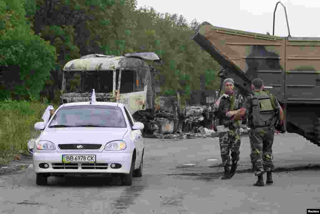 Pro-Russian separatists stand guard at a check-point as a car drives past outside Luhansk, Ukraine, June 18, 2014.