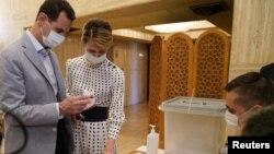 Presiden Suriah Bashar al-Assad dan istrinya Asma saat memasukkan surat suara Pemilu Parlemen di sebuah TPS di Damaskus, Suriah, 19 Juli 2020. (Foto: SANA/Handout via REUTERS)