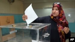 An Omani woman casts her vote at a polling station in Muscat, on October 15, 2011.