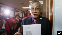 Former party list Congressman and now senatorial candidate Walden Bello holds documents as he arrives at the Commission on Elections seeking to postpone the April 8, 2016 fight between Filipino boxer and senatorial candidate Manny Pacquiao and Timothy Bradley, Feb. 22, 2016 in Manila, Philippines.
