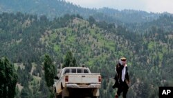 FILE - A Taliban militant is seen walking in Pakistan's tribal region of North Waziristan. Aug. 12, 2013. American author Paul Overby was hoping to reach to the region when he went missing in May of 2014.