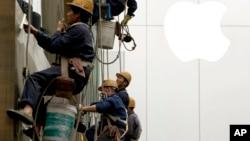 4月10日在北京,工人們在清洗一座建築物的窗子