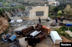 Palestinians check the damage after Israeli forces demolished a house in the village of Al-Walaja near Bethlehem, in the Israeli-occupied West Bank, Feb. 11, 2019.
