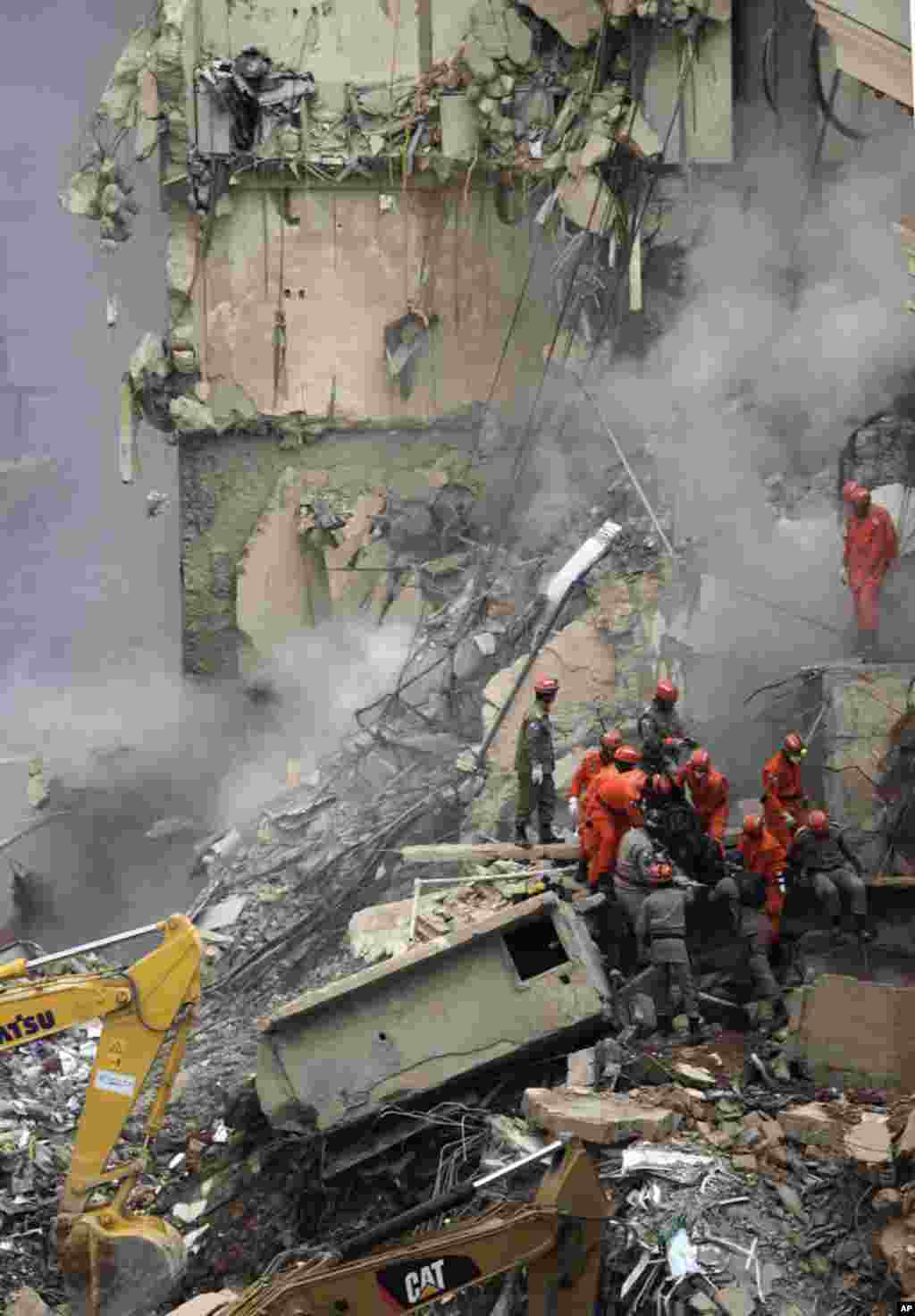 Firefighters carry the body of a victim among the debris of a collapsed building in Rio de Janeiro. January 26, 2012. (Reuters)