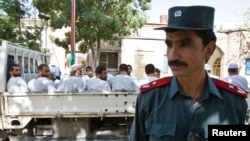 An Afghan police officer stands guard in front of a truck carrying Afghan prisoners on their way to court in Herat, western Afghanistan, August 16, 2009.