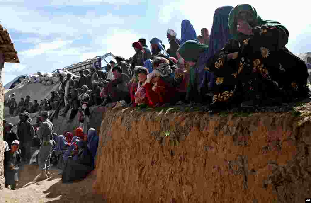 Survivors wait to receive food donations near the site of the landslide that buried Abi-Barik village in Badakhshan province, northeastern Afghanistan, May 6, 2014.
