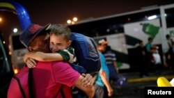 Josmer Rivas, 7, quien viajo en bus desde Caracas con su mamá, abraza a su papá a su llegada a la estación de Guayaquil, Ecuador. Noviembre 10, 2017.