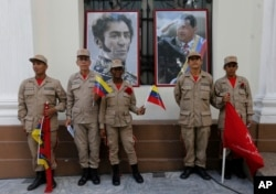 Militia members pose for a photo next to images of Venezuelan independence hero Simon Bolivar, left, and the late President Hugo Chavez, outside Venezuela's National Assembly, in Caracas, Aug. 4, 2017.