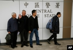 Four protest leaders, from right, Benny Tai Yiu-ting, Chan Kin-man, Chu Yiu-ming and former Cardinal Joseph Zen, walk inside the police station in Hong Kong as they surrender to police, Dec. 3, 2014.