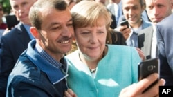 FILE - German chancellor Angela Merkel poses for a selfie with a refugee in a facility for arriving refugees in Berlin, Sept. 9, 2015.
