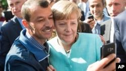 Kanselir Jerman berpose untuk swafoto bersama pengungsi di sebuah fasilitas di Berlin (9/9).