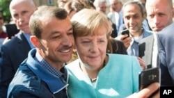 برلن میں ایک پناہ گزین چانسلر مرکل کے ساتھ سیلفی لے رہا ہے