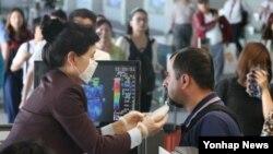 지난 1일 중동발 여객기를 타고 인천공항에 도착한 한 외국인들이 발열 감시 적외선 카메라에 열이 감지되자 메르스 감염 여부를 검사하기 위해 정밀 체온측정을 받고 있다.