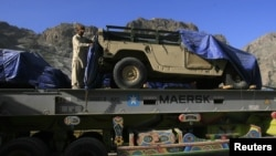 A man stands atop of a truck, carrying supplies for NATO Forces, as he covers a vehicle with plastic sheet before he departed for Afghanistan through the Pakistan-Afghan border town of Torkham October 10, 2010. Pakistani authorities on Sunday reopened a b