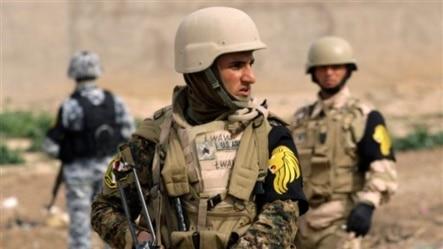 Một chiến binh người Kurd (giữa) đứng gác cùng một cảnh sát Iraq (trái) và một binh sĩ quân đội Iraq ở ngoại ô Kirkuk, phía bắc Baghdad, Iraq.
