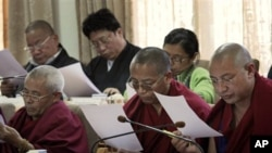 Tibetan parliamentarians read a printed message by the Dalai Lama during the eleventh session of the Tibetan parliament-in-exile in Dharmsala, India, Monday, March 14, 2011. The Tibetan spiritual leader Dalai Lama Thursday said that he will give up his po