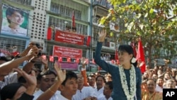 Burma's pro-democracy leader Aung San Suu Kyi waves at supporters during the opening ceremony of the National League for Democracy party's Mingalar Taung Nyunt township branch office in Rangoon, January 17, 2012.