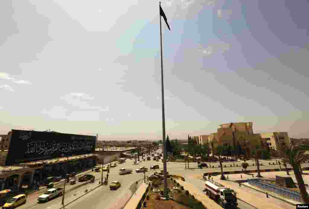 The flag of the Islamist Syrian rebel group Jabhat al-Nusra flies over the main square of Raqqa, Syria, May 1, 2013.