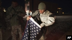 A soldier with the 3rd Brigade Combat Team, 1st Cavalry Division folds up a U.S. flag outside their Mine Resistant Ambush Protected (MRAP) vehicle before leaving Camp Adder near Nasiriyah to travel with the last U.S. military convoy to leave Iraq Sunday,