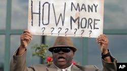 2015年4月8日一名抗議者在南卡羅萊納州北查爾斯頓市政廳前舉牌抗議兩天前警察槍殺沃爾特•司考特。