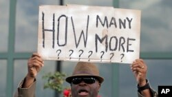 FILE - Rev. Arthur Prioleau holds a sign during a protest in the shooting death of Walter Scott at city hall in North Charleston, S.C., Wednesday, April 8, 2015. Scott was killed by a North Charleston police officer after a traffic stop.