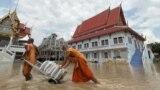 Biksu Buddha menarik gerobak yang membawa karung pasir untuk melindungi sebuah kuil dari banjir di Provinsi Ayutthaya, Thailand, 27 September 2021. (Foto: Dailynews via REUTERS)