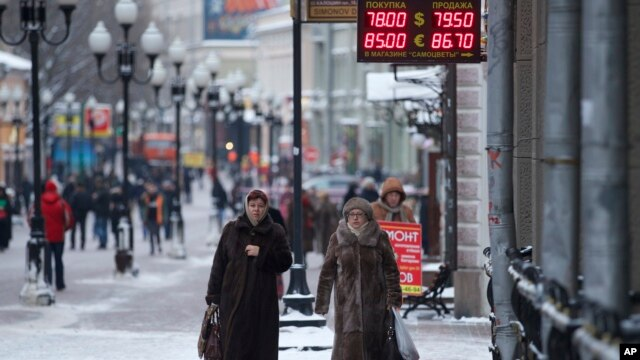 Women pass a currency exchange kiosk on a street in Moscow, Russia, Jan. 18, 2016. The Russian ruble, battered by weak oil prices, on Monday dropped to new lows and broke an all-time record against the euro.
