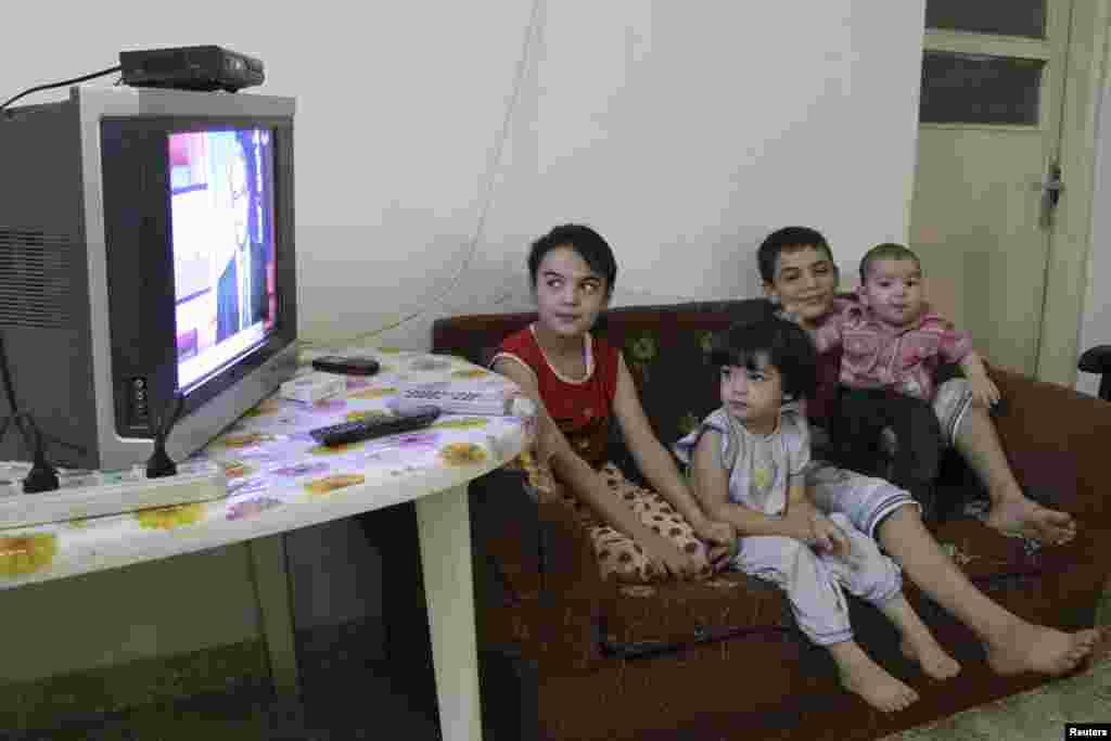지난달 29일 요르단 암만의 시리아 난민캠프 아동들이 시리아 상황을 보도하는 TV방송을 시청하고 있다.