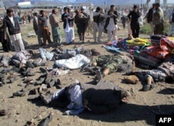 Pakistani men gather beside the bodies of victims of a bomb explosion at a market in Parachinar, the capital of Kurram tribal district, Dec. 13, 2015.