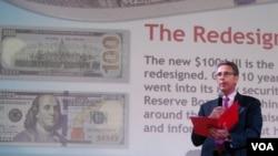 Pejabat Bank Sentral Amerika, Michael Lambert memperkenalkan desain baru uang kertas 100 dolar Amerika di @America, Jakarta, 23 Oktober 2013 (VOA/Iris Gera).