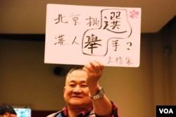 有支持普選人士在研討會高舉標語,諷刺北京當局搞假普選