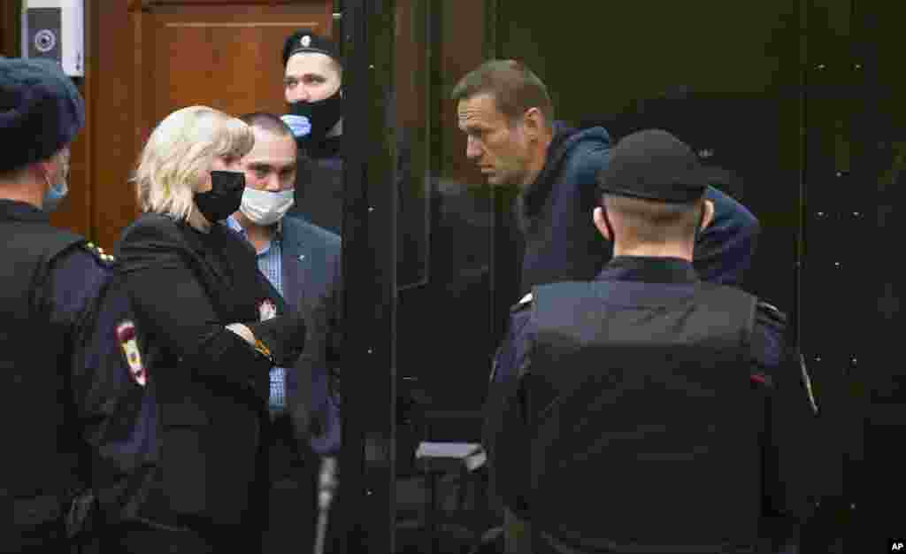 In this handout photo provided by Moscow City Court, opposition leader Alexei Navalny talks to his lawyers during a hearing to a motion from the Russian prison service to convert his suspended sentence from the 2014 criminal conviction into a real prison term in the Moscow City Court.
